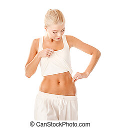 fit woman measuring fat level on her waist - fitness and...