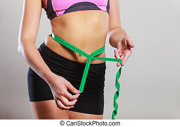 Fit woman measuring her belly with measure tape