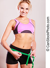 Fit woman measuring her hips waist
