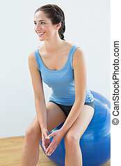 Fit woman on exercise ball looking away