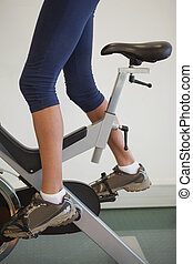 Fit woman on the spin bike at the gym