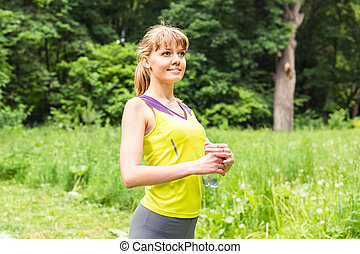 Fit woman outdoors holding a bottle of water