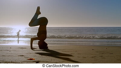 Fit woman performing yoga in the beach 4k - Fit woman...