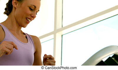 Fit woman running on treadmill - Fit woman running on...