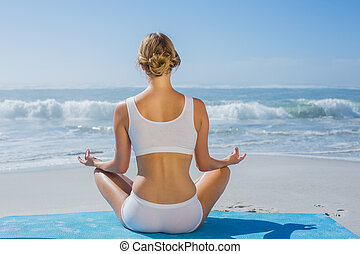 fit woman sitting on grass in lotus pose smiling at camera