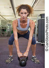 Fit woman squatting with kettlebell at the gym