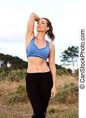 Fit woman standing outside with hand in hair