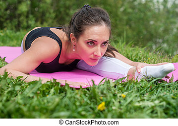 Fit woman stretching, exercising on mat in nature.