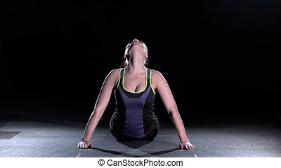 Fit woman stretching her back to warm up, on black