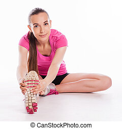 Fit woman stretching her leg to war