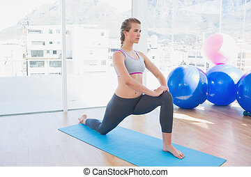 Fit woman stretching leg in fitness