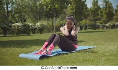 Fit woman training abs on sports mat in city park - Sporty...