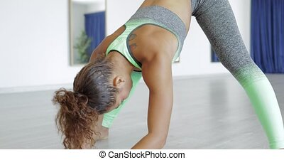 Fit woman training alone in studio - Curly sportswoman in...
