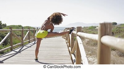 Fit woman training on pier - Back view of fit ethnic woman...