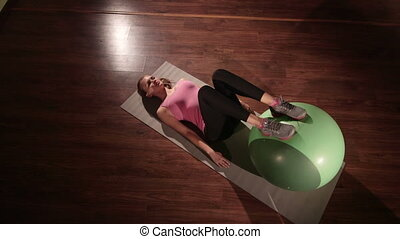 Fit woman training on the floor with ball in health fitness club doing exercise