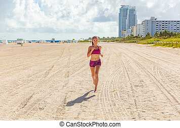 Fit woman training outdoors running barefoot on Miami south beach run jogging workout female Asian athlete. Happy healthy fitness person cardio jog in sun summer lifestyle.