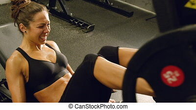Fit woman trains legs with heavy weights in fitness gym -...