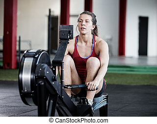 Fit Woman Using Rowing Machine - Full length of fit woman...