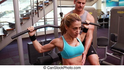 Fit woman using the weight machine