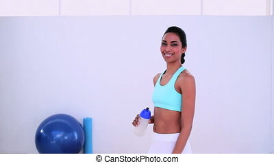 Fit woman walking and drinking