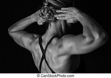 Fit woman with shaped muscles on back in artistic conversion