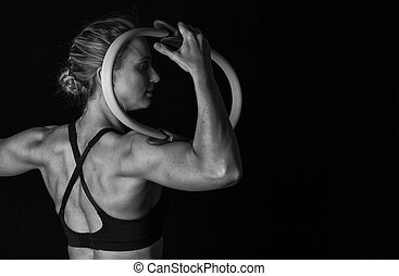 Fit woman with shaped muscles on her back and training hoop artistic conversion