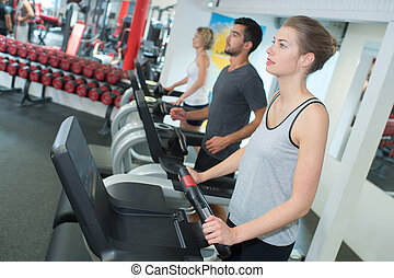 fit woman working out on stepping machine in gym