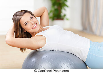 Fit woman - Young fit woman exercising with fitness ball at ...