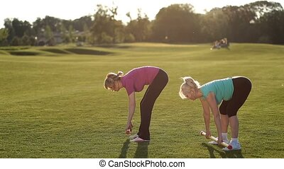 Charming sporty fit adult women performing deadlift exercise with weight body bars on park lawn at sunset. Side view. Active senior females in sport clothes doing weight lifting workout with body bars outdoors over beautiful landscape background.