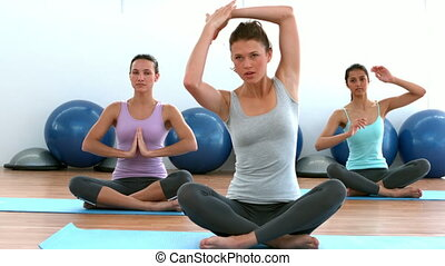 Fit women doing yoga together in st