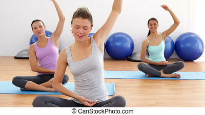 Fit women doing yoga together