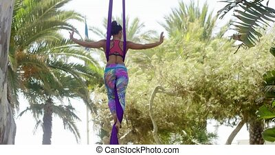 Fit young acrobat dancer practicing her routine hanging...
