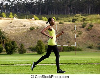 Fit young african american woman jogging outdoors in a park