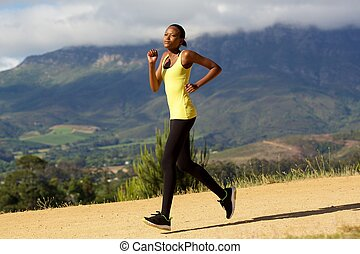 Fit young african woman jogging outdoors in nature