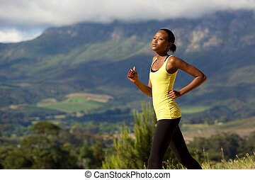 Fit young african woman running outdoors in nature