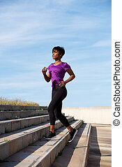 Fit young african woman running up stairs