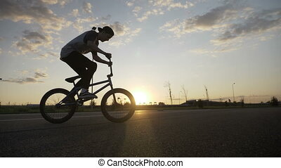 Fit young biker jumping on bike and doing ollie hop trick...