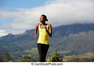 Fit young black woman running in nature