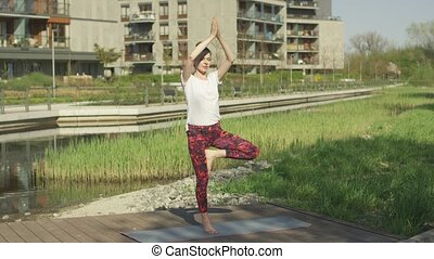 Fit young brunette training yoga pose outside - Young...