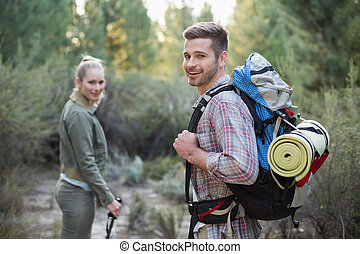 Fit young couple exploring a wooded area in the countryside