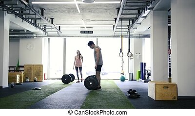 Fit young couple in gym lifting heavy barbell, flexing muscles. Dead lift.