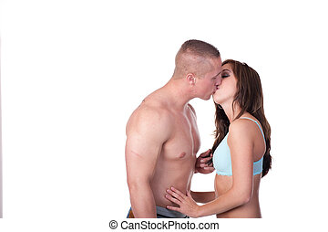 An attractive young couple, dressed for the beach, kissing. Shot against a white background.