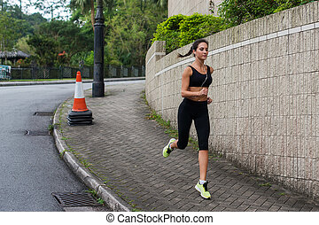 Fit young female jogger jogging on sidewalk in suburban area. Pretty girl working out outdoors.