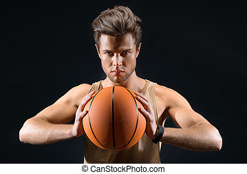 Fit young man playing basketball