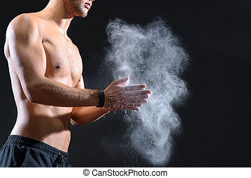 Fit young man rubbing arms with talc