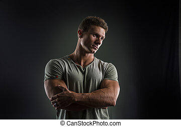 Fit young man standing confident, arms crossed