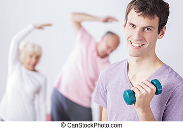 Fit young physiotherapist teaching older people exercises