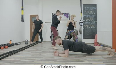 Fit young students exercising and preparing in a cross fit gym to obtain their personal training license