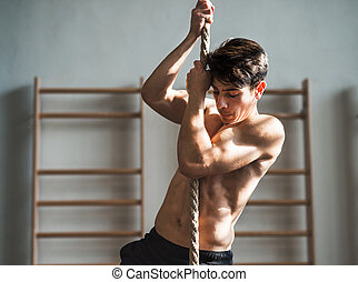 Fit young topless man in gym climbing a rope.
