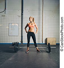 Fit young woman at gym with barbell